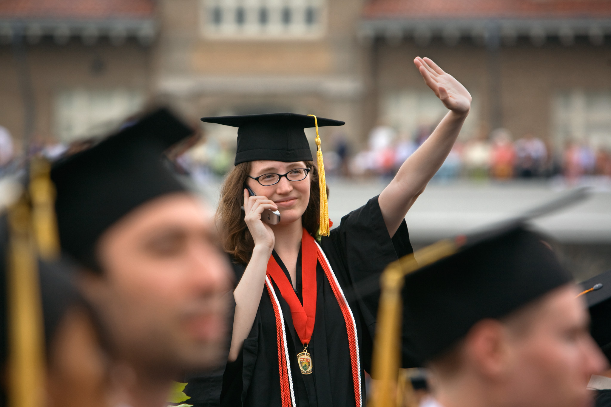 Student on phone at graduation