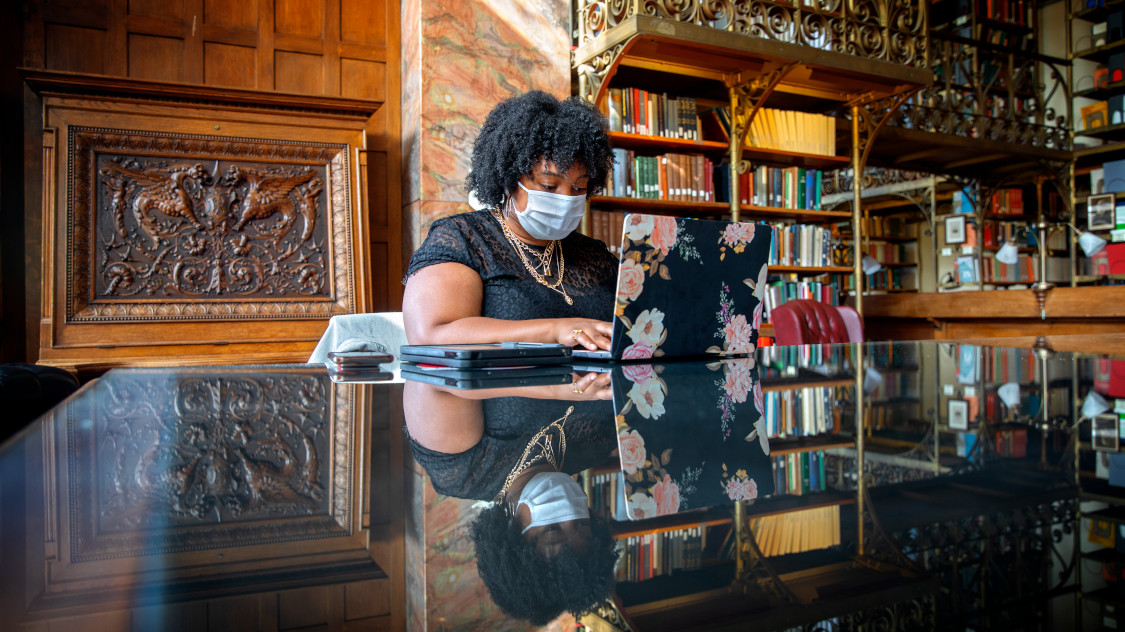A student wearing a mask works in their reserved study space in the AD White Library